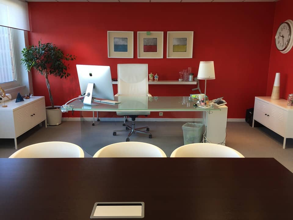 Office furniture including glass table and chairs in office with red wall