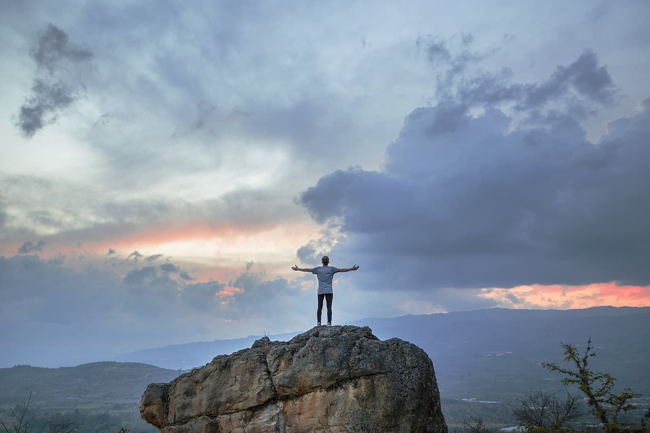 man standing on the top of the hill