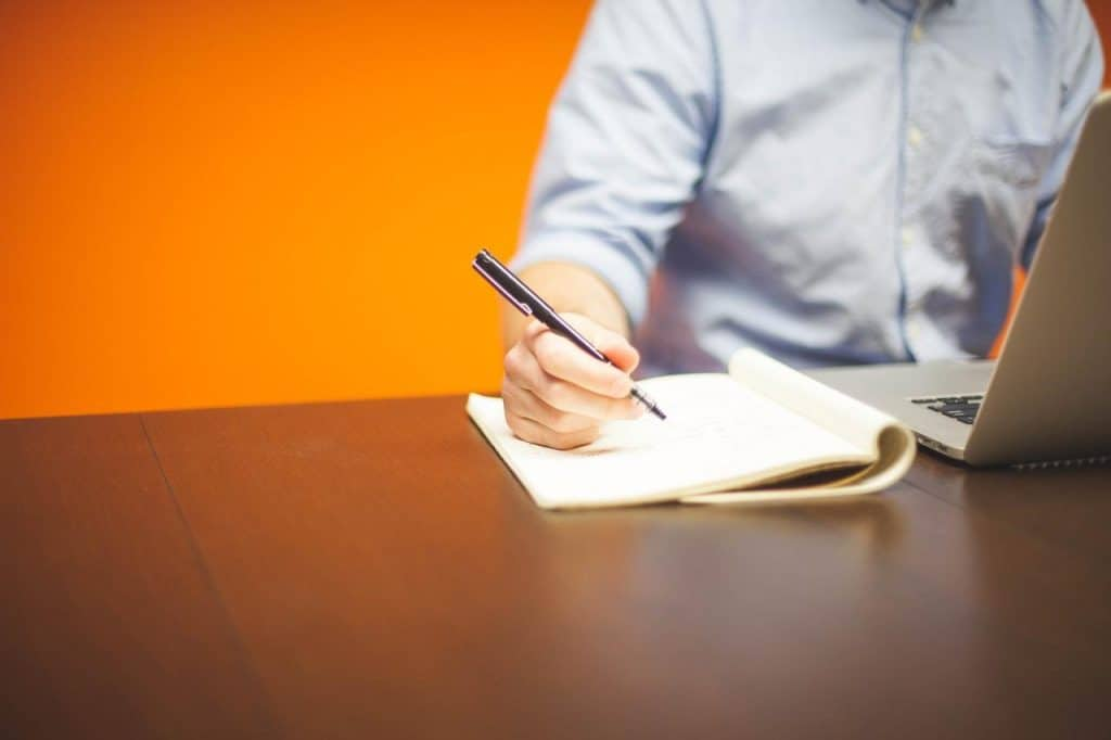 Become a Successful Wholesale Supplier in 30 Days - person at desk writing in notepad