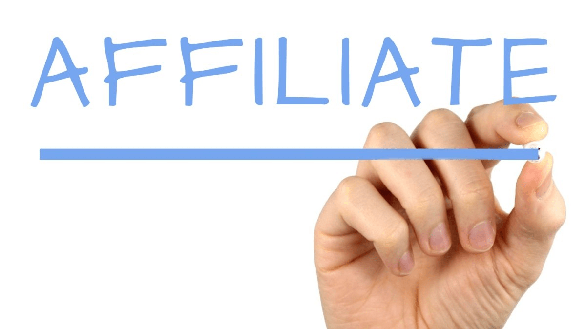 Hand holding pen and writing the word affiliate
