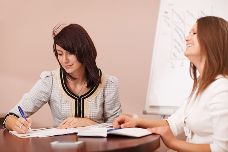 Two female coworkers in a meeting, one writing notes while the other smiles happily at something being said