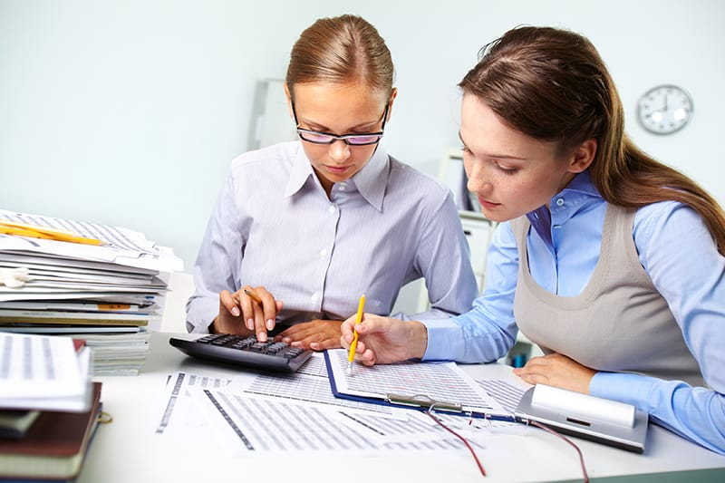 Concentrated business women reviewing accounting report