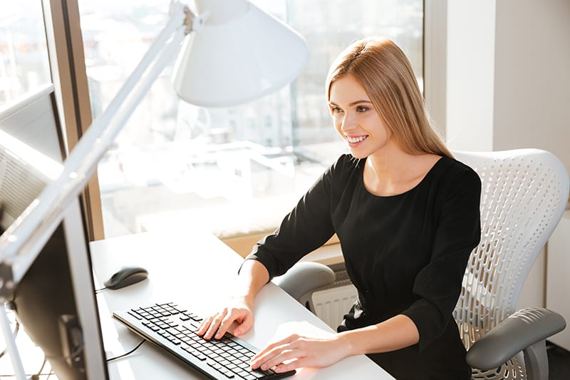 Photo of joyful young lady worker using computer in office and typing by keyboard. Look at computer.