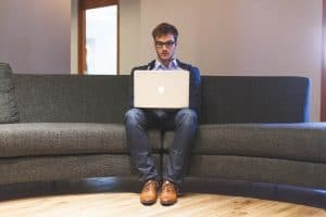 Man sitting on sofa with laptop on knees