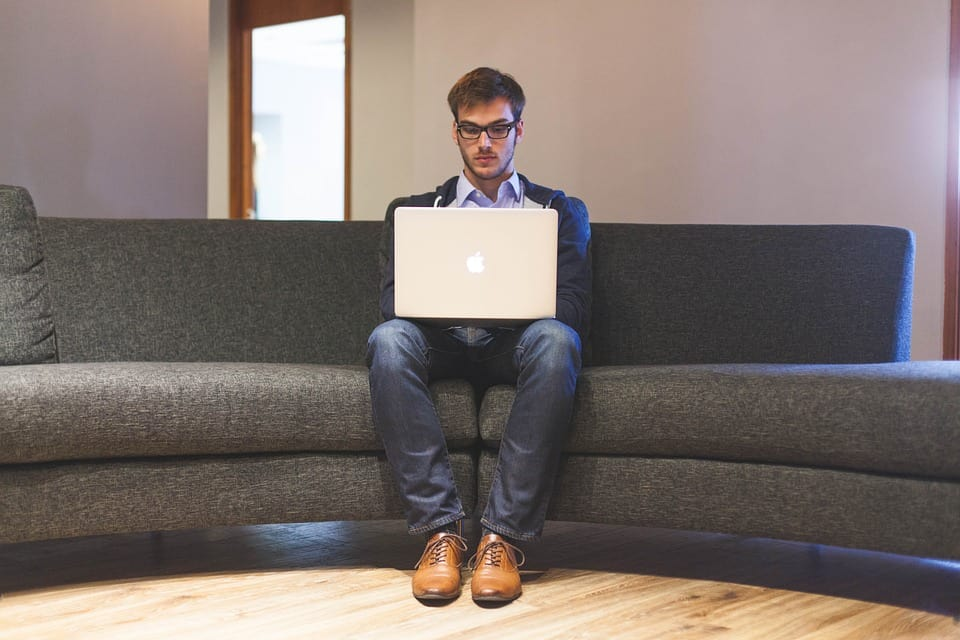 Young man sitting on grey sofa with laptop on knees