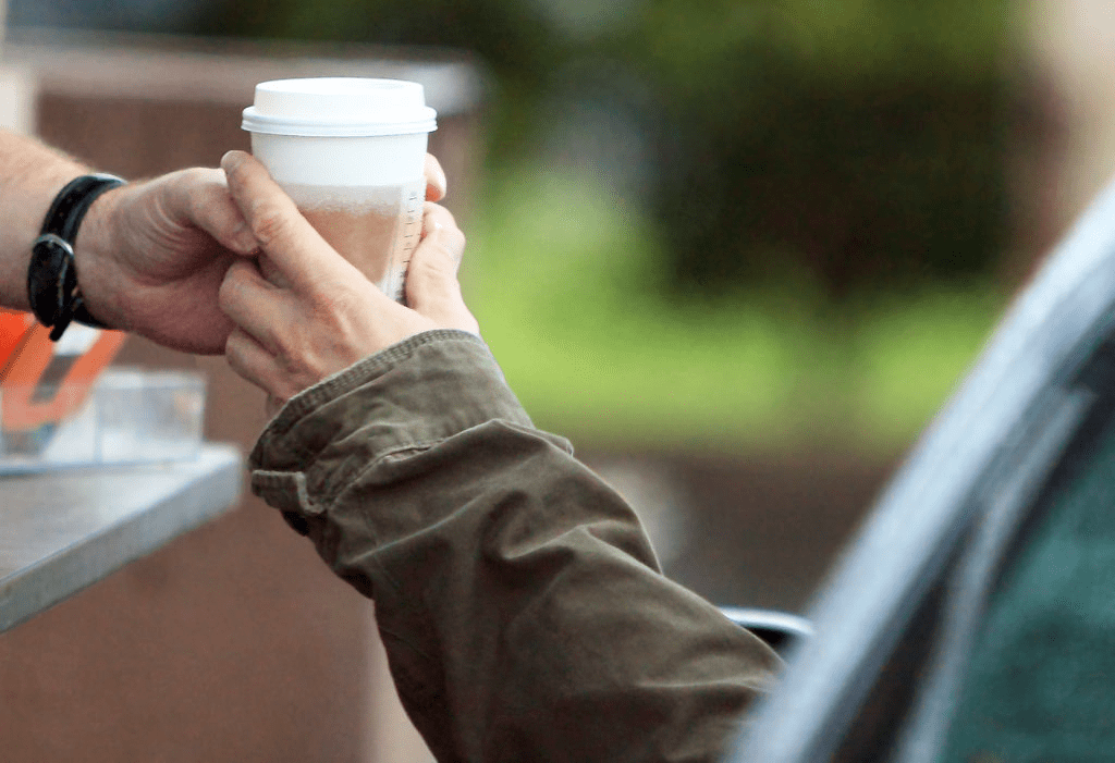 someone handing a hot drink to ciustomer at drive through take away