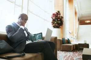 Businessman sitting on sofa working using cell phone and laptop. African male executive waiting in hotel lobby.