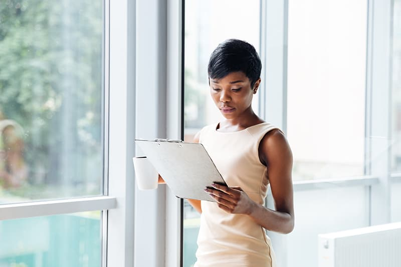 Beautiful african american young businesswoman with cup of coffee holding clipboard and reading in office