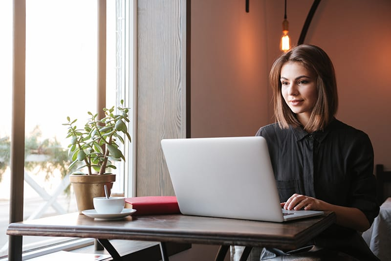 Image of pretty young lady sitting at the table in cafe and looking at laptop computer.