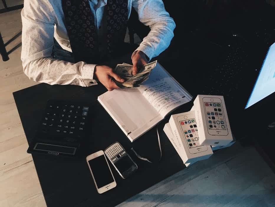 man with dollars in hand desk book mobile phone calculator