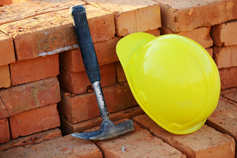 Under construction, helmet with hammer and bricks for building site