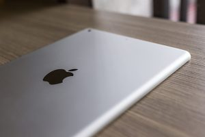 Logo of Apple in back Apple iPad air on wood desk.