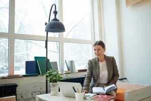 Senior financial manager wrapped up in work: she sitting in cozy small cafe with panoramic windows and preparing annual accounts on laptop, waist-up portrait