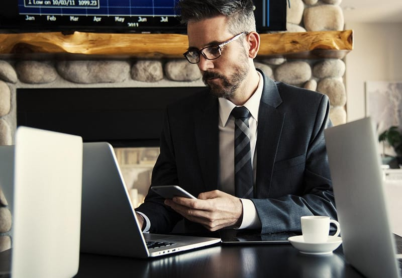 person holding mobile phone and looking at laptop screen