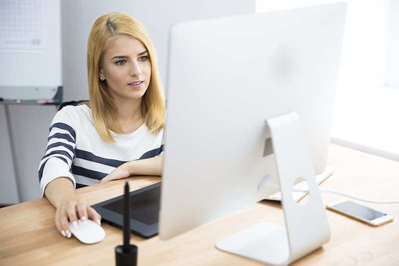 Casual young female photo editor working on computer in office