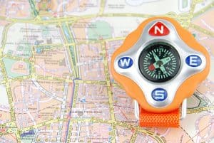 orange compass on a city map (travel/orientaion concept)
