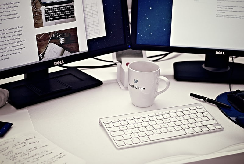 monitors showing ideas for businesses - next to keyboard and mug on desk