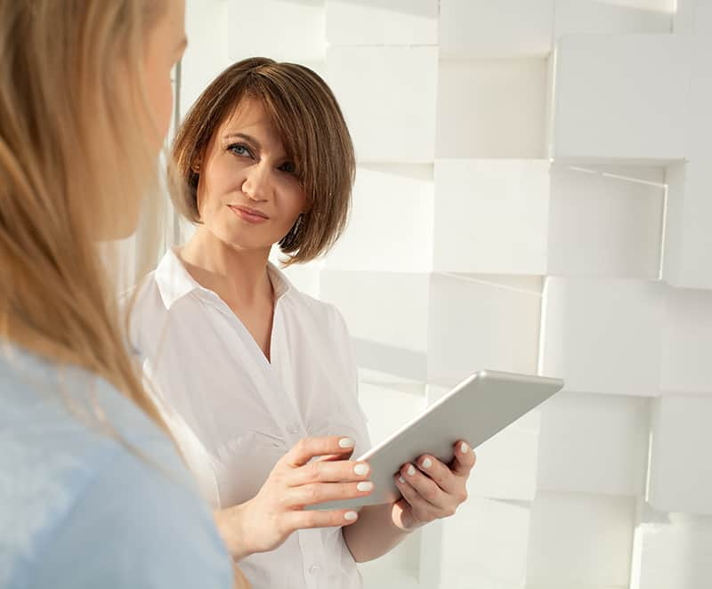 Businesswoman with tablet looking at her colleague while standing against of modern white wall.