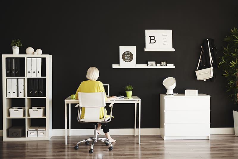 Rear view of businesswoman working at home office - decluttering ideas for your home office