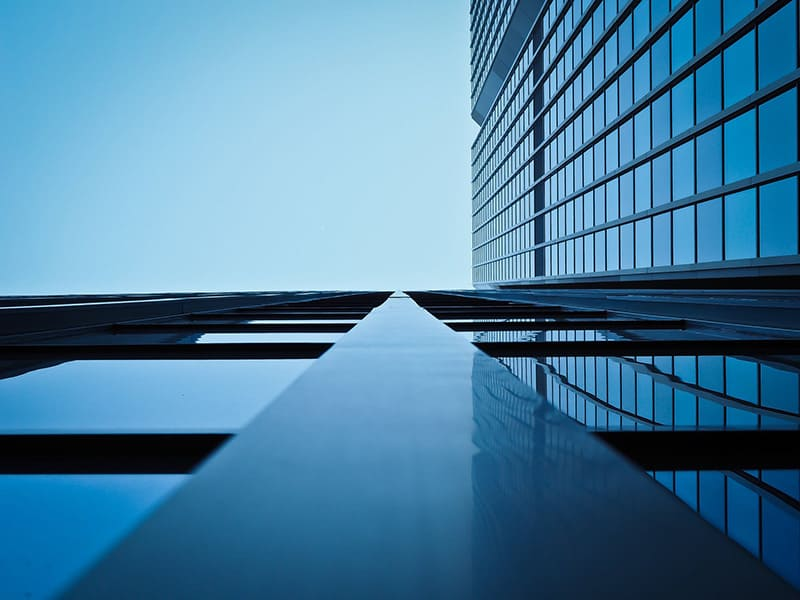 view of glass office building from ground looking up