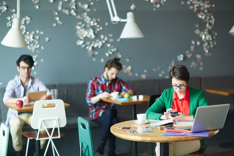 Group of young casual business people working in co-working space