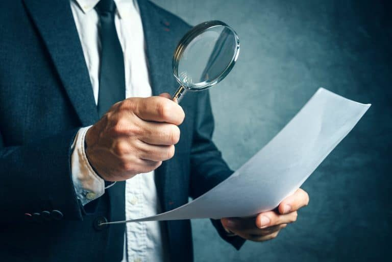 Man in suit looking at document through magnifying glass