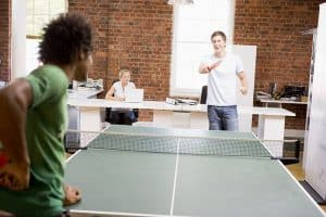 Work Perks That Your Millennial Employees Will Appreciate - Two men in office space playing ping pong