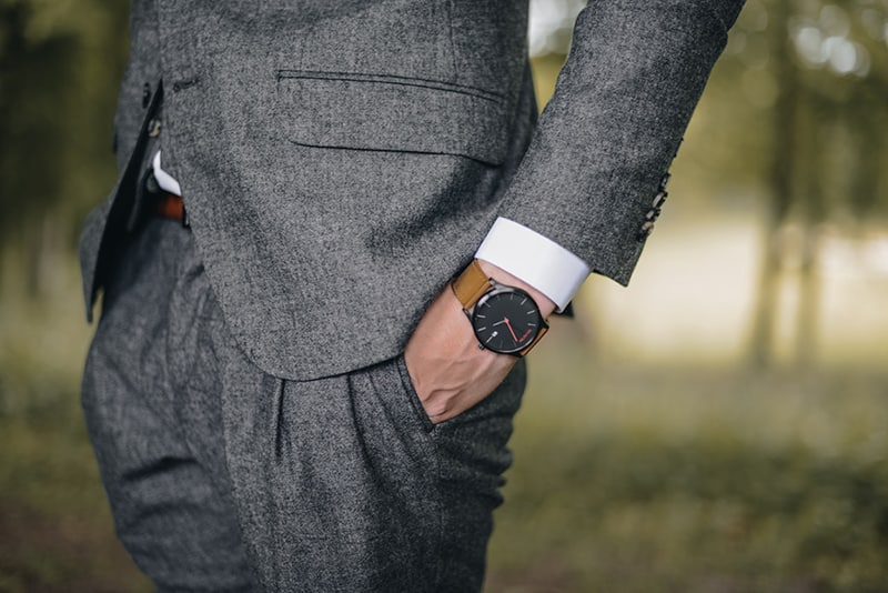 man dressed in smart suit white shirt cuff showing brown watch on wrist