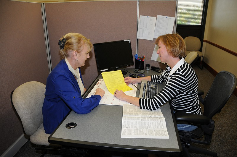 two ladies looking ad document across a desk