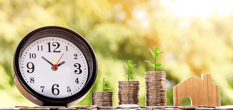 Clock next to stacks of coins with plants on top, growing investment