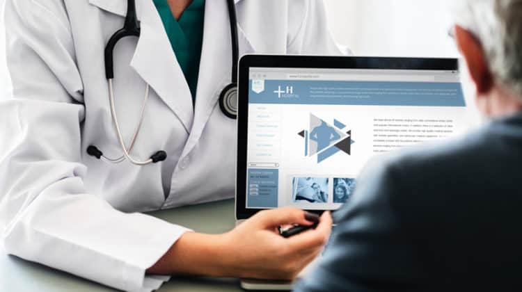 doctor pointing at laptop screen showing it to patient