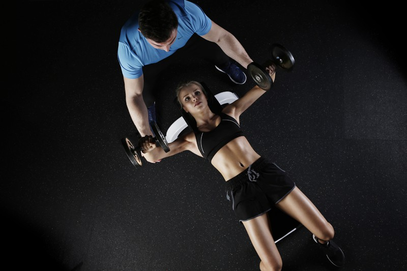 lady lying on bench with wights personal trainer on hand