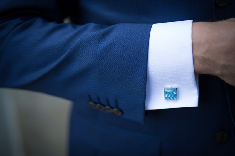 person wearing blue suit and white shirt with cufflinks
