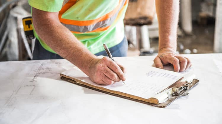 Workman writing on a clipboard placed on top of blueprints