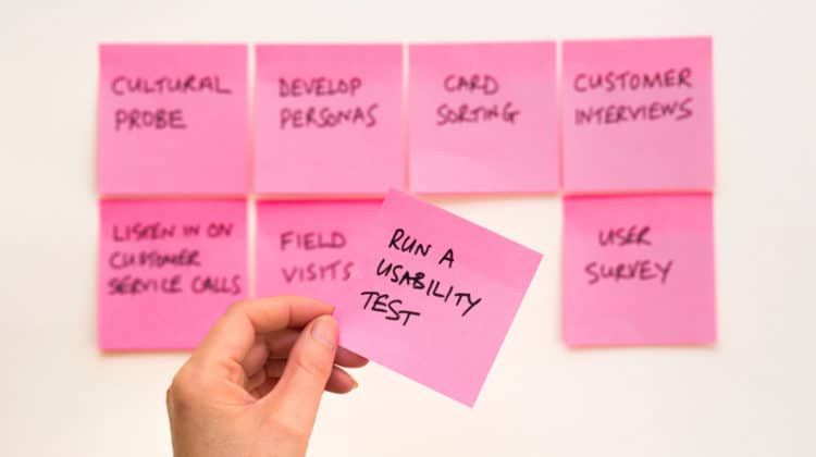 person holding pink post it sticky note