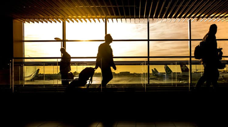 Silhouette of people in airport at dawn