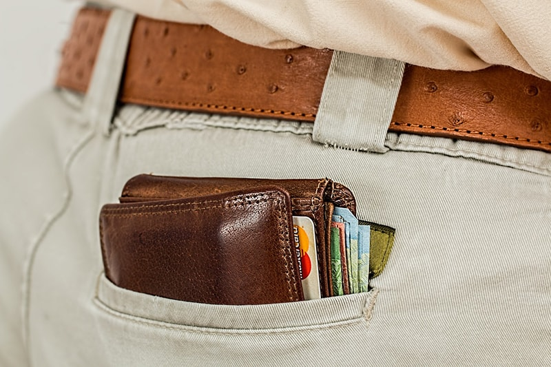 Close up of wallet containing cash and card in back trouser pocket
