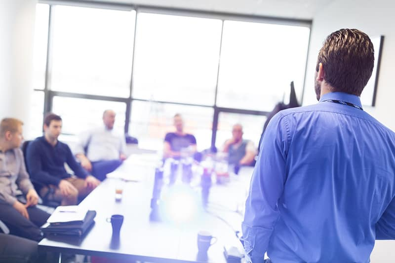 People sitting around conference table listening to someone delivering training
