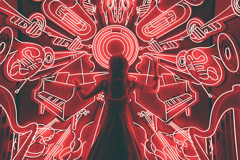 Woman conducting music to neon musical instruments
