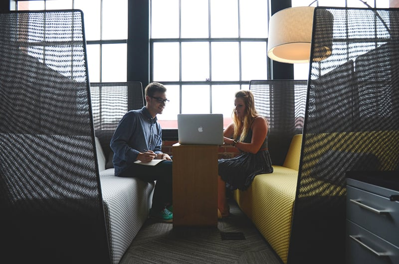 man and lady sitting in a booth looking at laptop computer