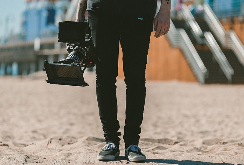 Photographer/videographer holding camera on the beach