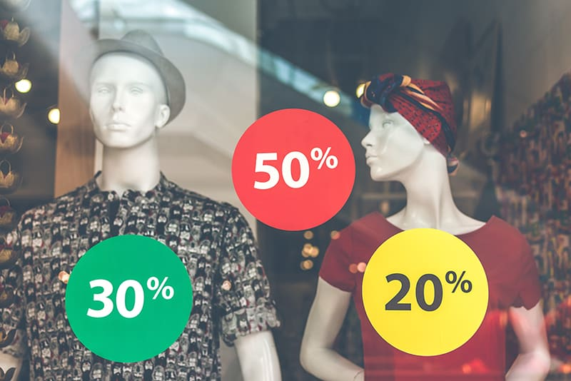 Male and female mannequin in shop window with sale stickers