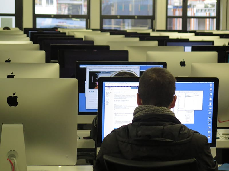 Rear view of man working at a computer in office