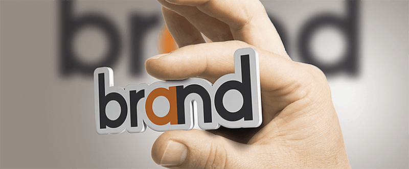 person holding the word brand between fingers