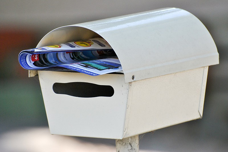 white mail box with leaflet in it