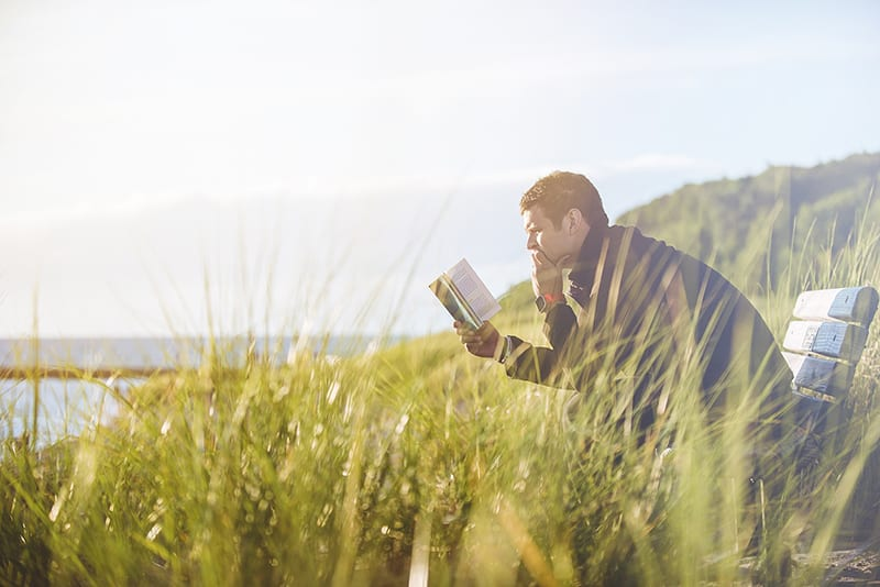 MAn reading book on bench long grass sea view in background