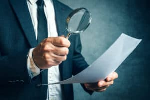 Man looking at document through a magnifying glass