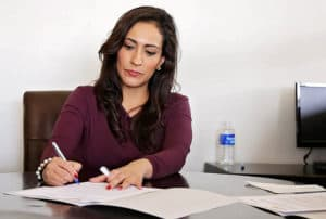 woman working in office signing paperwork