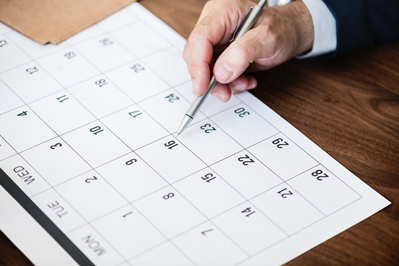 person pinpoint pen on calendar - Why Managing Employee Leave Properly Matters