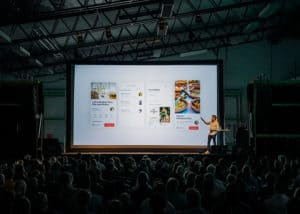 Person doing a business presentation standing in front of a large screen in front of people inside dim lit room